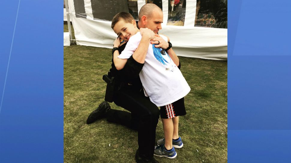 Zechariah Cartledge, 10, gets a hug from an officer during a recent run. He is often greeted by law enforcement officers who park their cars and flash their lights in support. (Courtesy of Cartledge family)