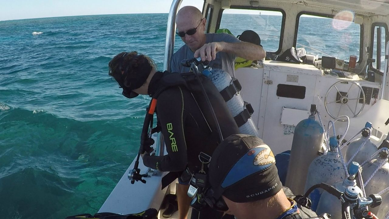 Boat operator Ron Stein assists Nova Southeastern University scientists with their scuba diving gear ahead of their coral treatment. (Vince Pecoraro/Spectrum News)