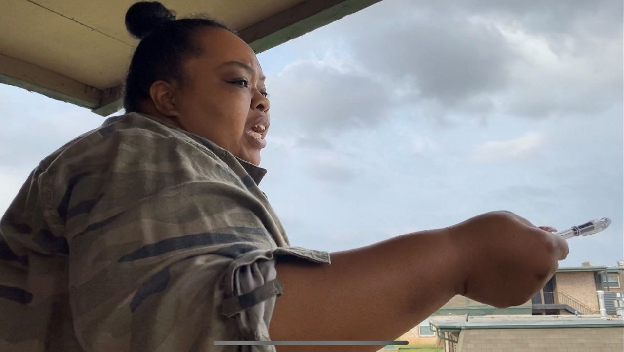 Taniquewa Brewster talks to her fellow Mount Carmel Apartment residents from her balcony. (Spectrum News 1)