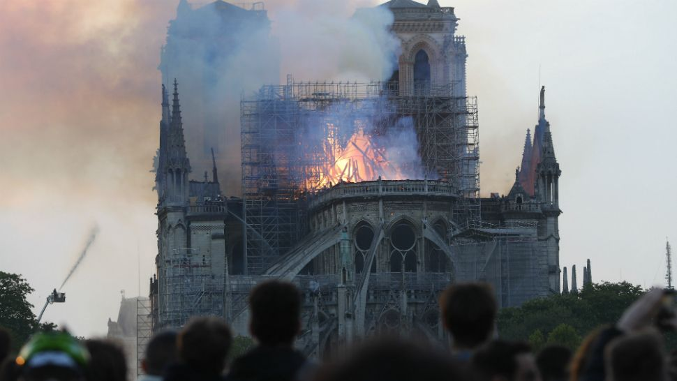 Horrified onlookers watch as the world-famous Notre Dame cathedral in the heart of Paris burns Monday, April 15, 2019. (Thibault Camus/AP)