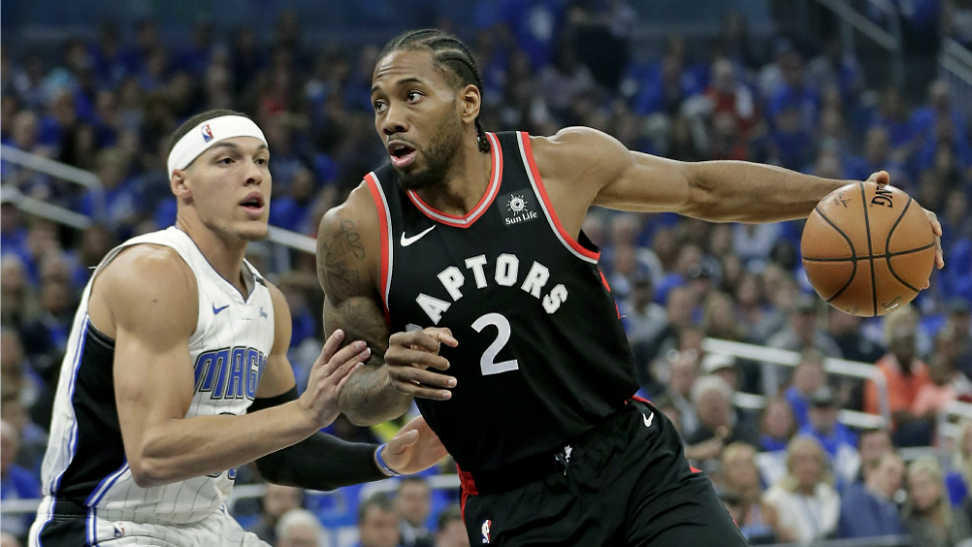 69f618abdbe The Toronto Raptors  Kawhi Leonard (center) drives to the basket against  the Orlando