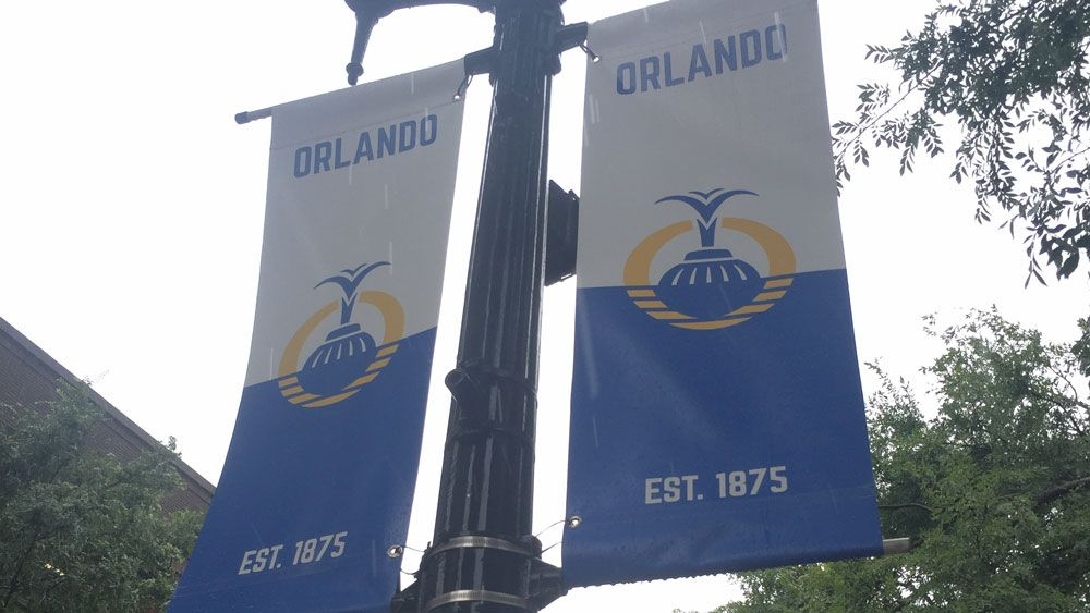 Rainwater drips from the Orlando lightpost flags in Downtown Orlando, May 14. (Christie Zizo, Staff)
