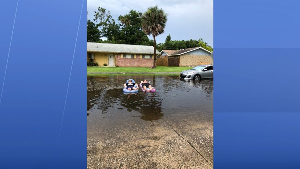 Residents are seen floating down their street in Port Orange at heavy rain flooded parts of the neighborhood. (Melissa Herlehy, viewer)