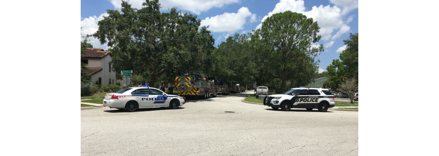 Orlando Police and firefighters surround an apartment building near Universal Orlando on Monday afternoon, where a man is reportedly is barricaded inside with 4 children. A police officer was shot there overnight. (Tony Rojek, staff)