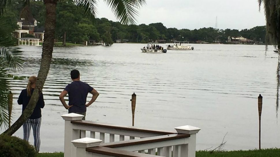 People watch as first responders conduct a search of Lake Maitland hours after a small plane crashed into the water Wednesday. The FAA said the plane took off from Orlando Executive Airport. (Asher Wildman/Spectrum News 13)