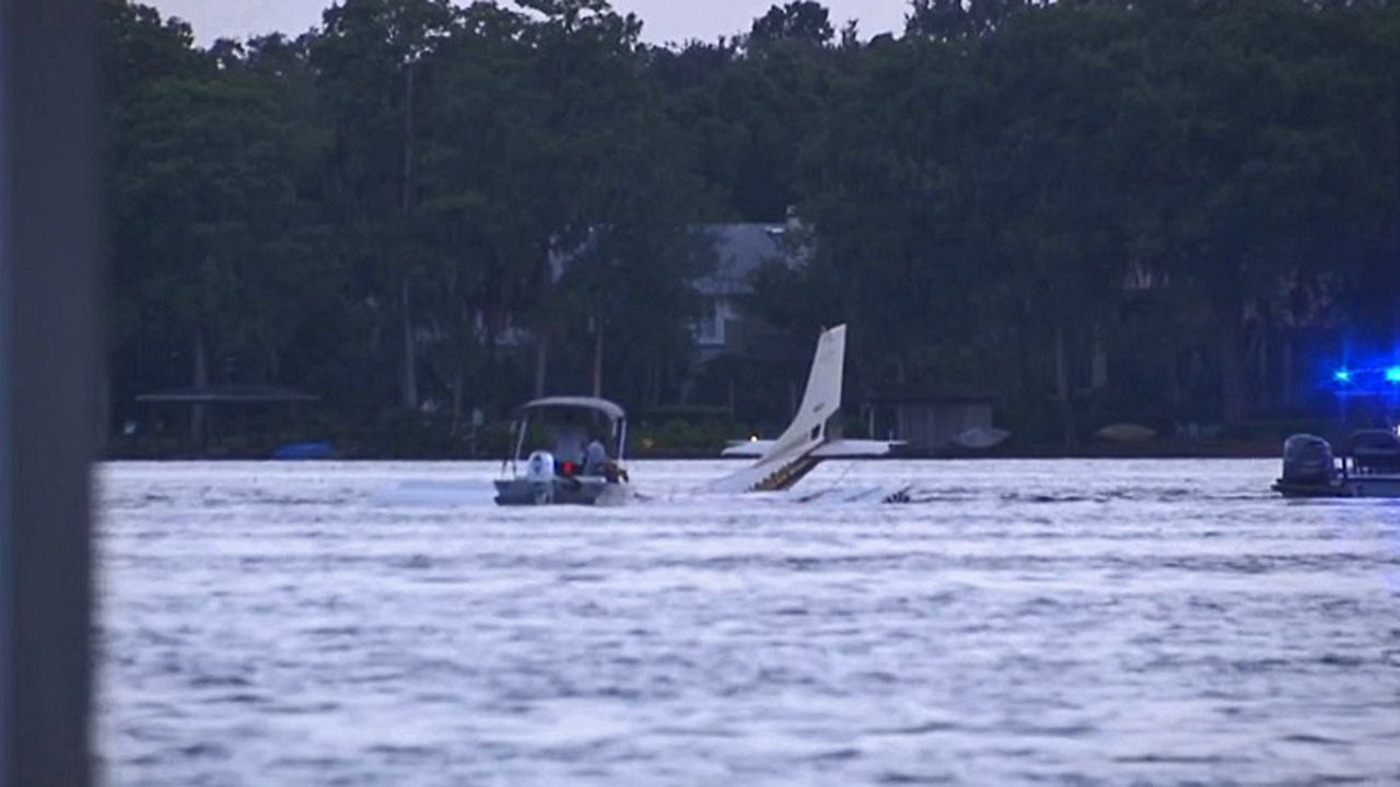 Crews work to tow a Cessna 182 out of Lake Maitland after it crashed into the water Wednesday. Two people were on board but did not survive. (Matt Fernandez/Spectrum News 13)
