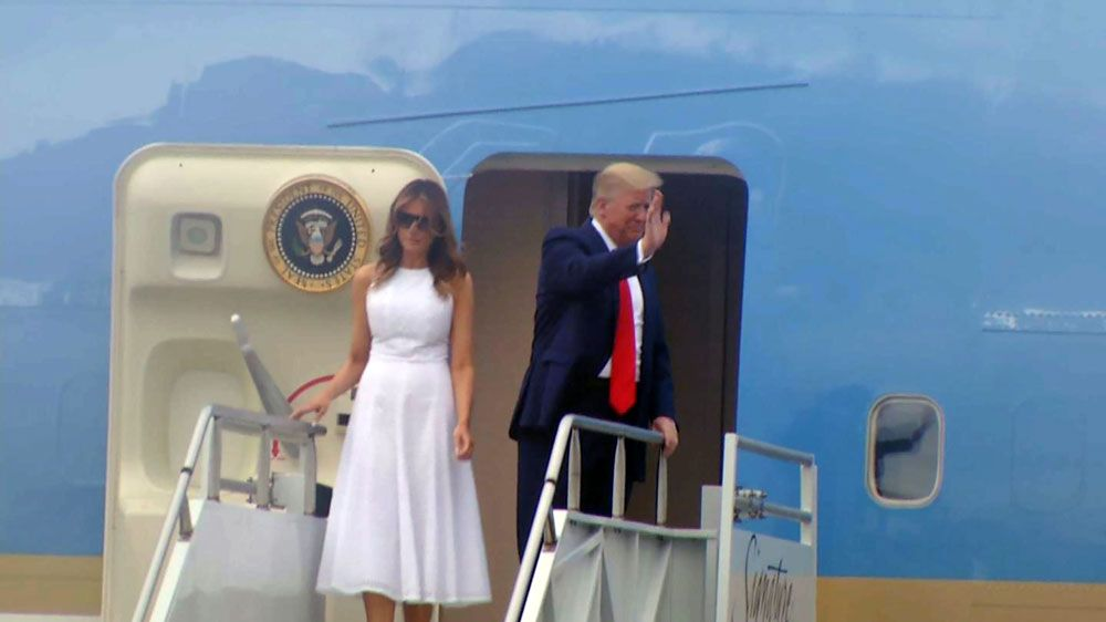 President Donald Trump and first lady Melania Trump wave from Air Force One moments after arriving at Orlando International Airport early Tuesday evening ahead of a campaign rally at the Amway Center. (Spectrum News)