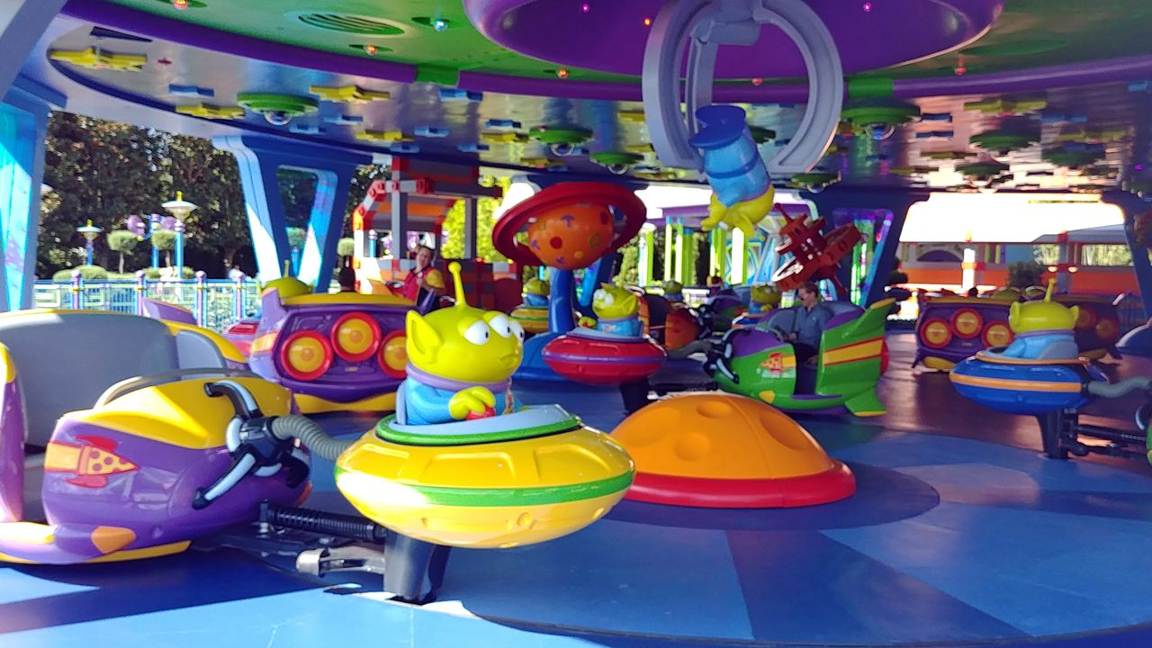"Alien Swirling Saucers features little green aliens pulling riders along in their flying saucers while ""The Claw"" looms overhead. (Ashley Carter, staff)"