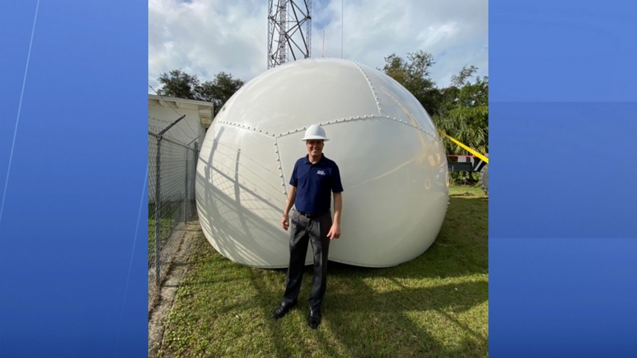 Spectrum News 13 Chief Meteorologist Bryan Karrick poses with Klystron 13's new radome in Cocoa.