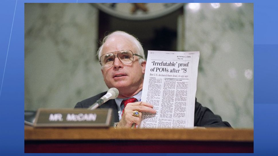FILE - In this June 24, 1992, file photo, Sen. John McCain, R-Ariz., holds up an article from the Washington Times during a hearing of the Senate Select Committee on POW/MIA Affairs on Capitol Hill in Washington. Arizona Sen. McCain, the war hero who became the GOP's standard-bearer in the 2008 election, has died. He was 81. His office says McCain died Saturday, Aug. 25, 2018. He had battled brain cancer. (AP Photo/John Duricka, File)