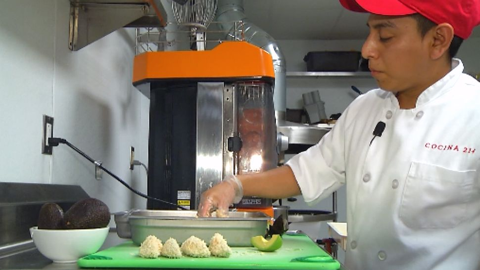 Chef Humberto Castillo dunks the avocado wedges into flour 3 times before coating in panko.