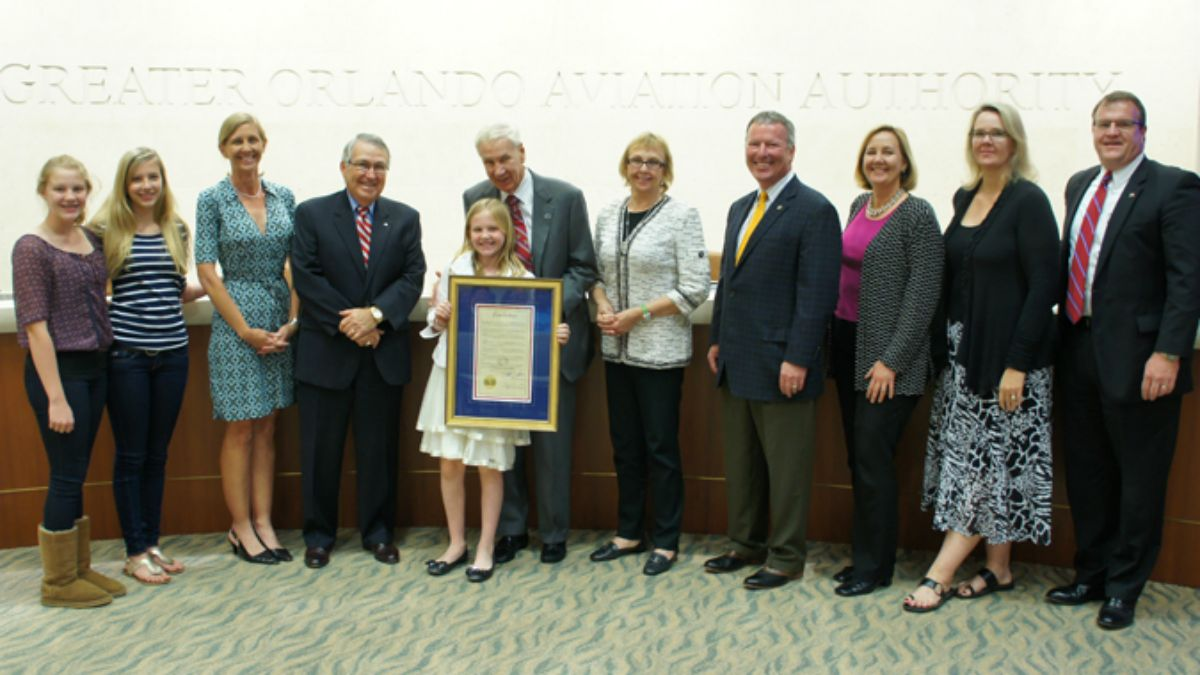 In 2012, Lou Frey (center, behind girl) was recognized by the Greater Orlando Aviation Authority. His work in Congress laid the groundwork for what became Orlando International Airport. (File)