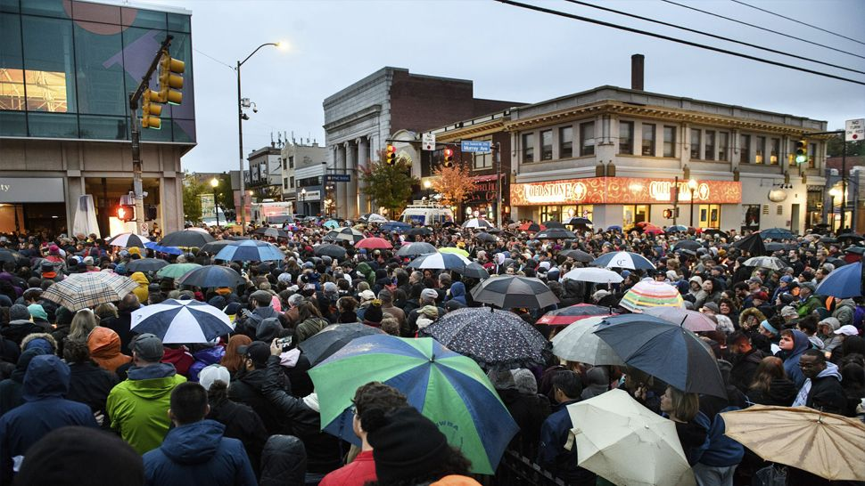 People gather for a vigil on Murray and Forbes Avenues, blocks from where an active shooter shot multiple people at Tree of Life Congregation synagogue on Saturday, Oct. 27, 2018, in the Squirrel Hill section of Pittsburgh. (Stephanie Strasburg/Pittsburgh Post-Gazette via AP)
