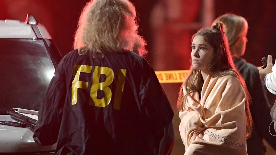 A possible witness speaks with the FBI about a shooting that left 11 dead, not including the gunman and a Ventura County Sheriff's Office deputy. (Associated Press)