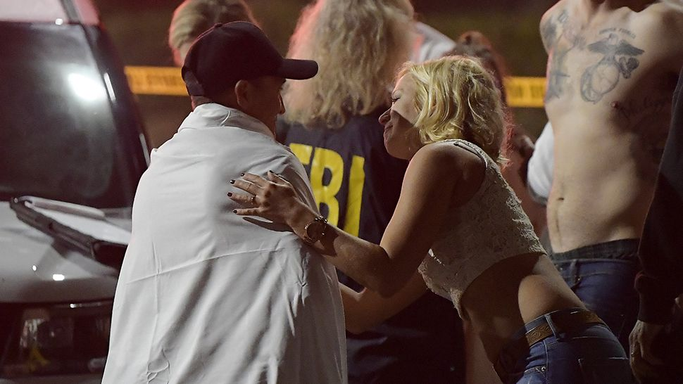 People comfort each other following a mass shooting at a bar in Southern California early Thursday that left 12 dead. (Associated Press)