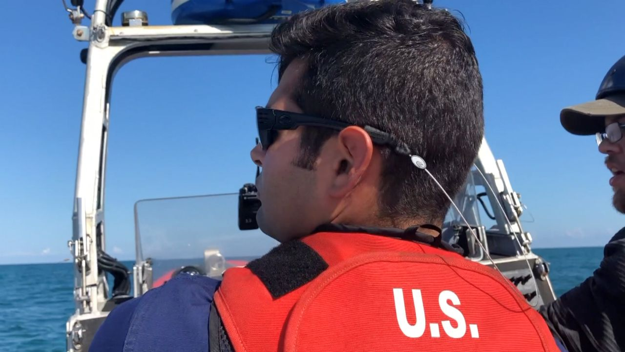 Petty Officer 2nd Class Luis Ortiz looks out over the waters off South Florida during a recent patrol mission. (Samantha-Jo Roth/Spectrum News)
