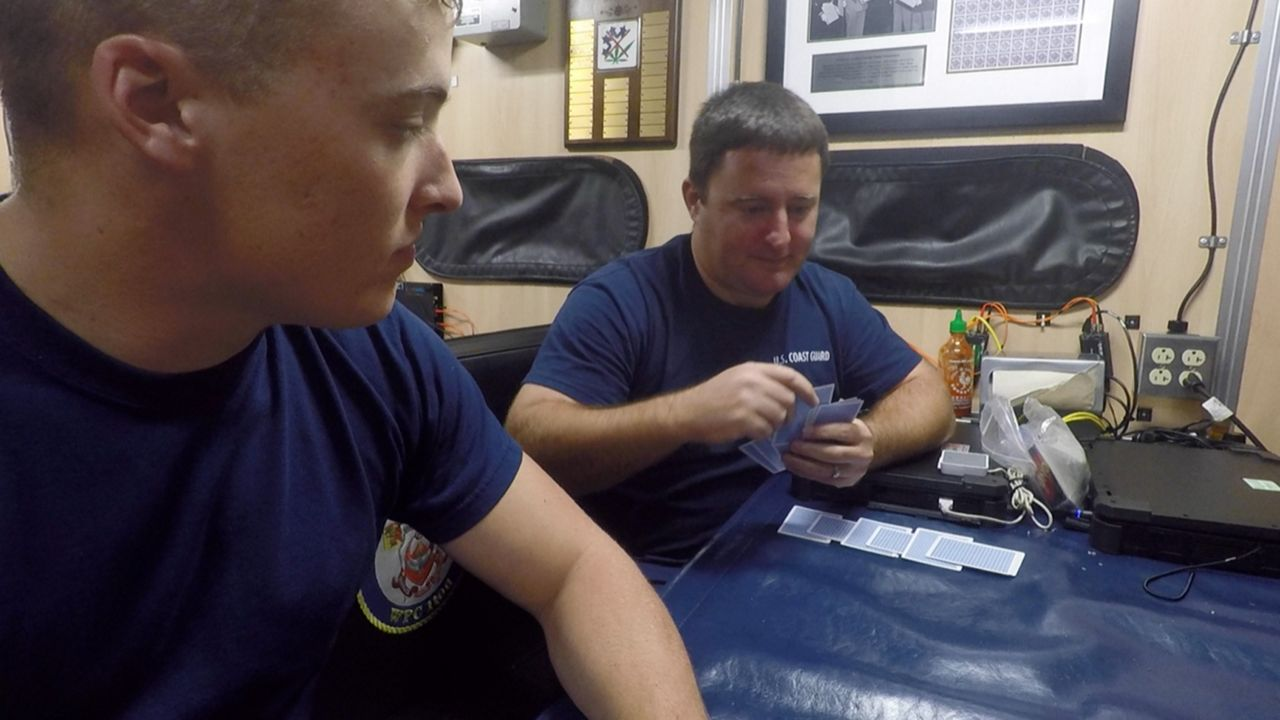 The men and women of the patrol play cards in their down time.