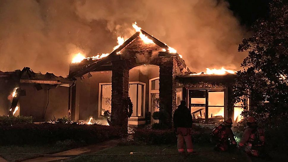A home on Oakwood Cove Lane in Orlando is engulfed in flames during the early morning hours of Tuesday, Dec. 11, 2018. No one was injured in the fire, according to officials. (Orange County Fire Rescue)