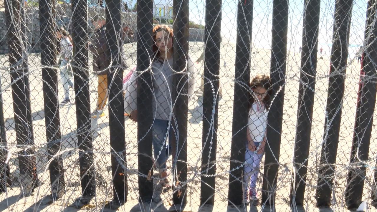 A mother and her children stand on the Mexican side of border fence.