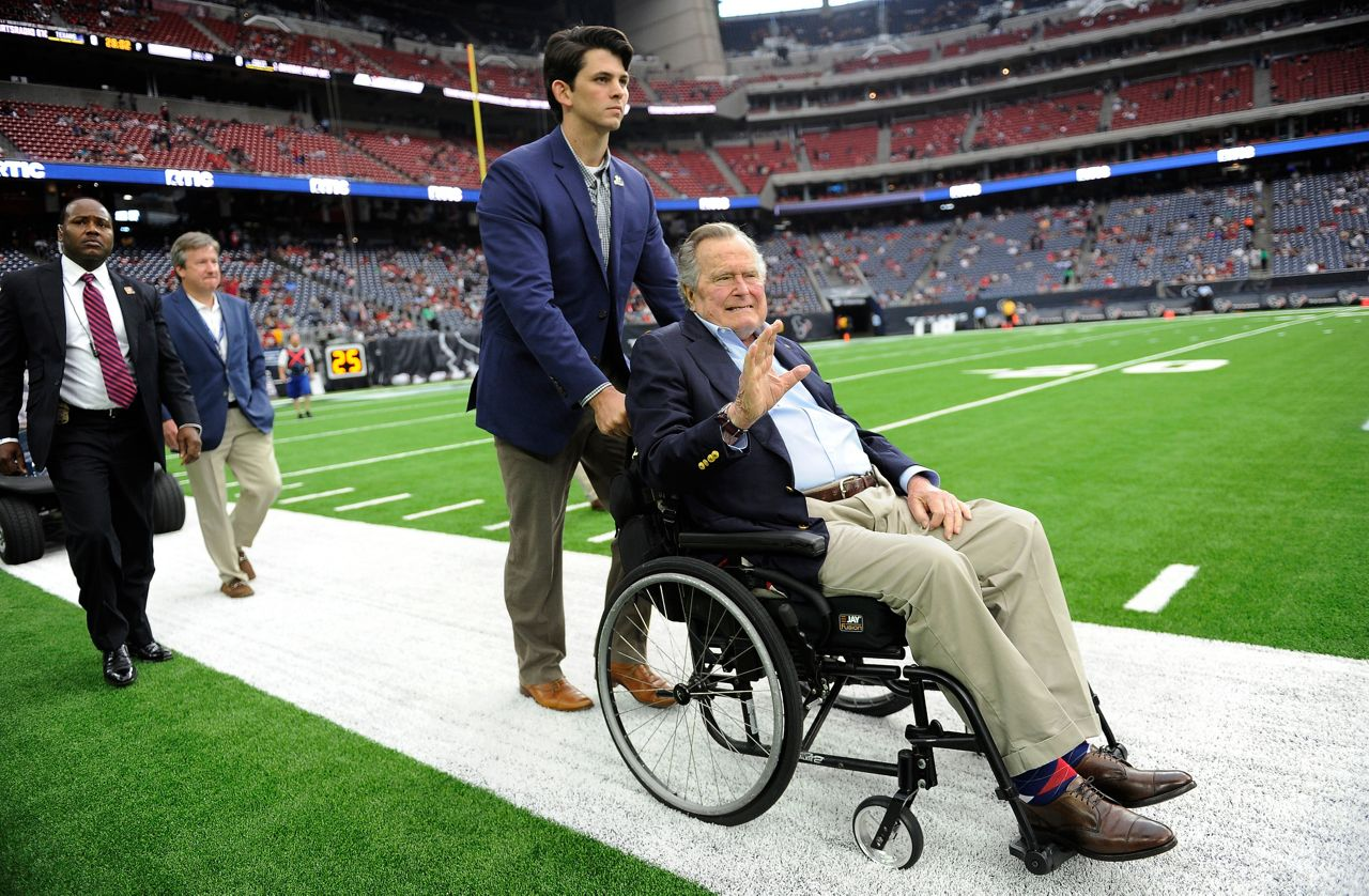Bush gets pushed in a wheelchair onto the Houston Texas field.