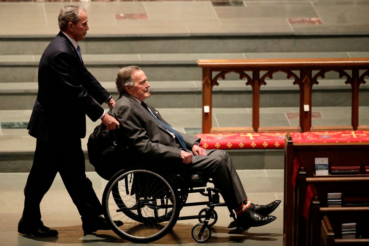 Bush being pushed into a church for his wife's funeral.