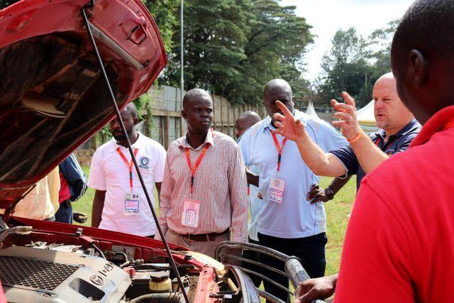 El voluntario de la Misión de Bomberos de África y los bomberos locales miran debajo del capó de un vehículo de bomberos (Foto: Provisto)