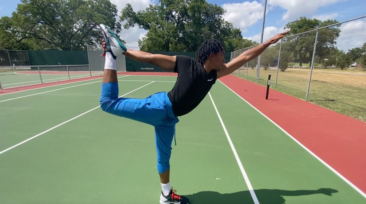 Chris Isolm stands in dancer's pose, a yoga position (Spectrum News)