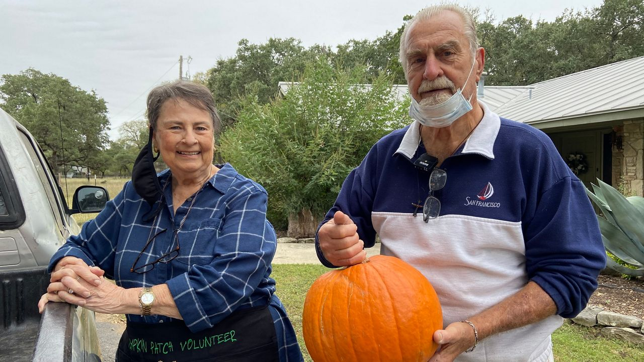 Connie and Ed Bremer pose with a pumpkin (Lauren Due/Spectrum News)