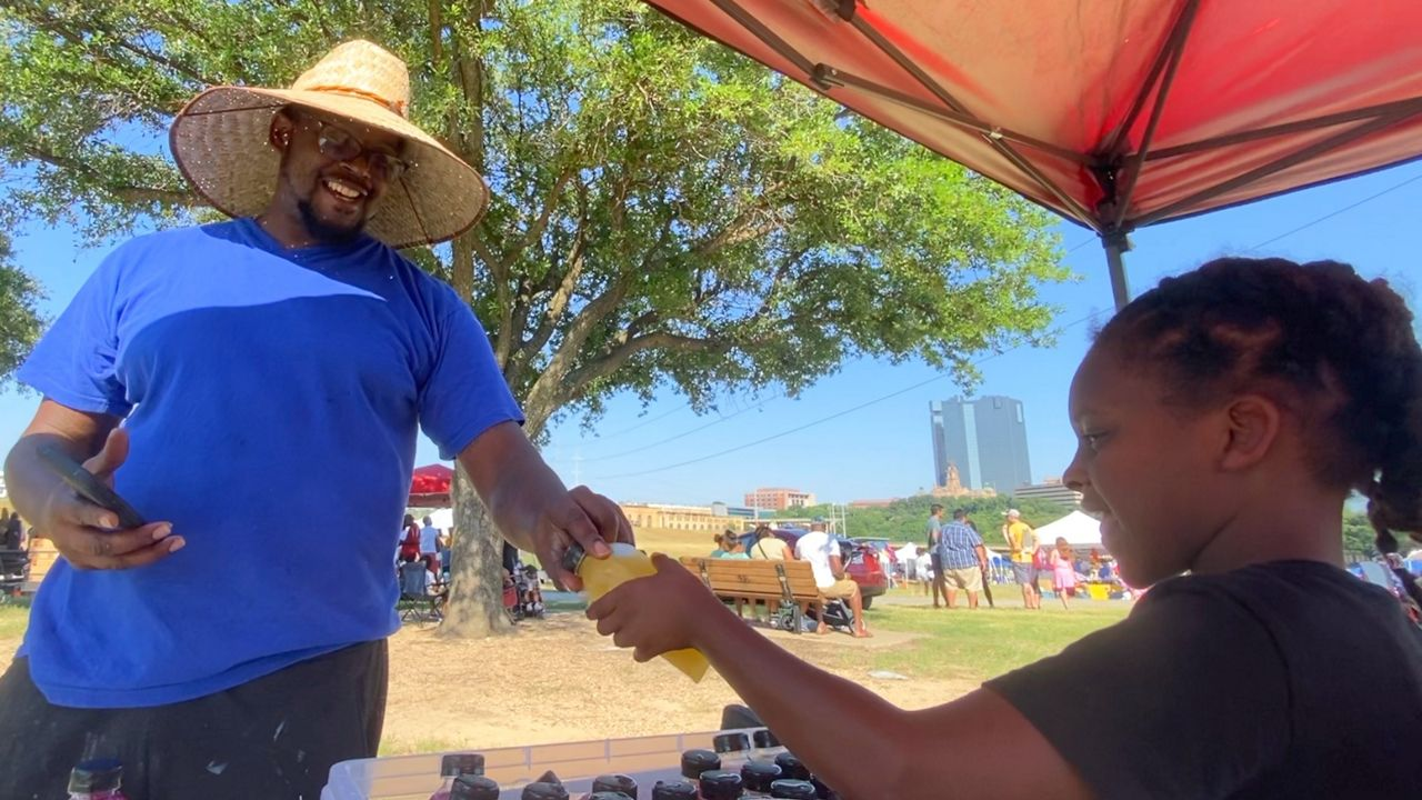 Pictured is 7-year-old E'Syntheis Chambers handing a new customer a bottle of one of his juice blends while at a Juneteenth event in Fort Worth. Chambers and his mother Roshanda White own EE Healthy Juicy Juice, an organic juicing business based in DeSoto, Texas. Credit, Lupe Zapata