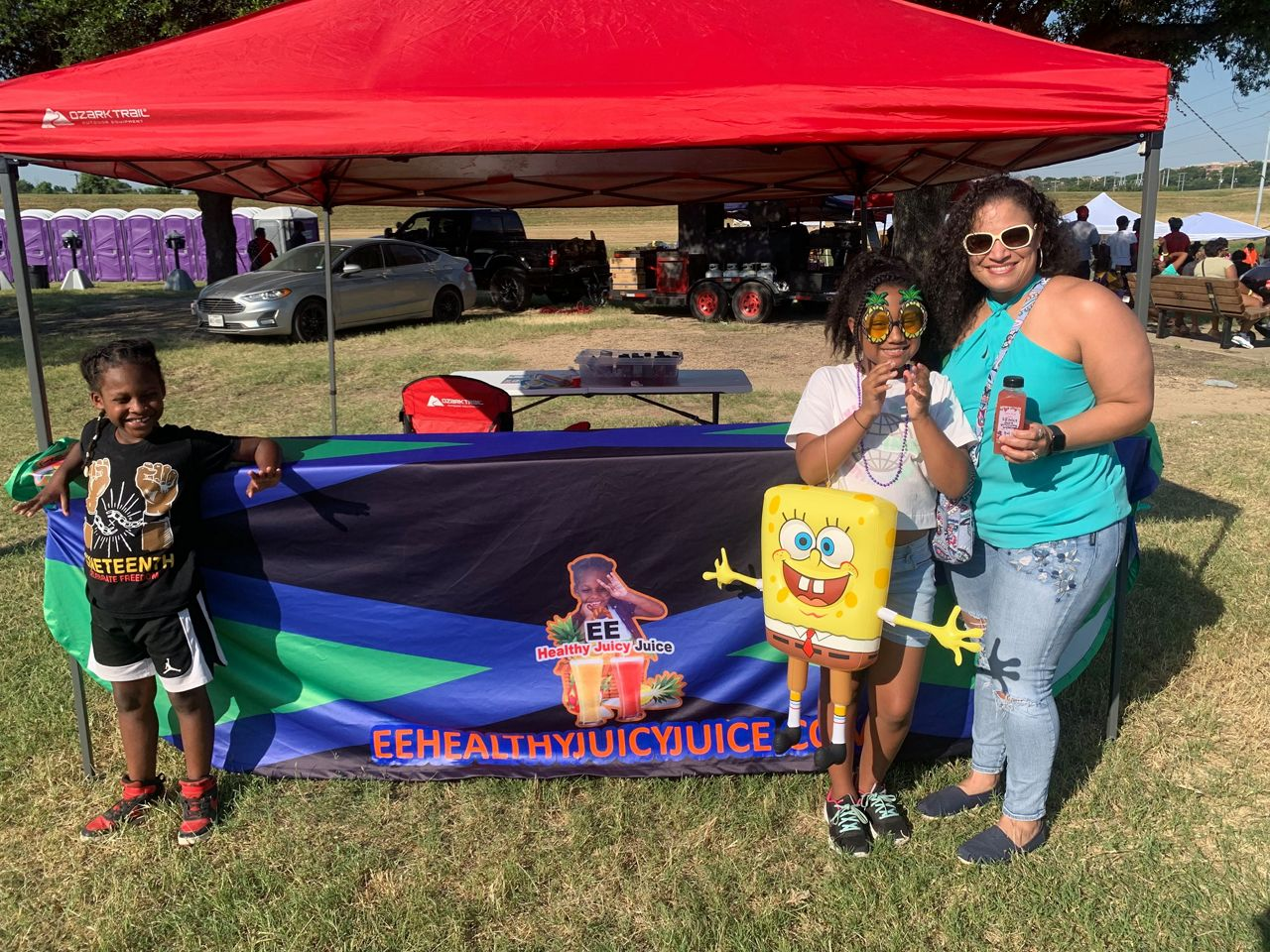 Pictured is E'Syntheis Chambers with two customers posing near his juice stand at a Juneteenth event in Fort Worth. At 7-years-old Chambers is the CEO of EE Healthy Juicy Juice, an organic juicing business he and his mother Roshanda White operate based in DeSoto, Texas. Credit, Lupe Zapata