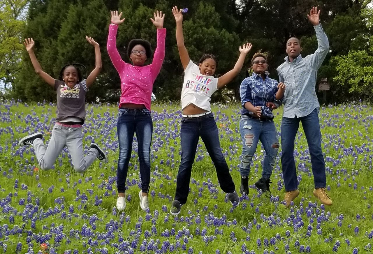 Family jumps in wildflower field.