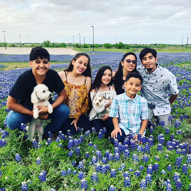 Ramos kids and their pets in a field of bluebonnets.