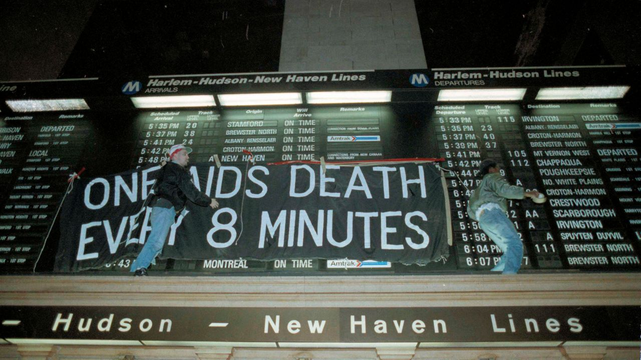 Members of the group Act-Up hang a banner across the train schedule board in New York's Grand Central Terminal. Hundreds of protesters marched through the station during rush hour to protest what they perceive as unfair spending for the war over AIDS treatment.