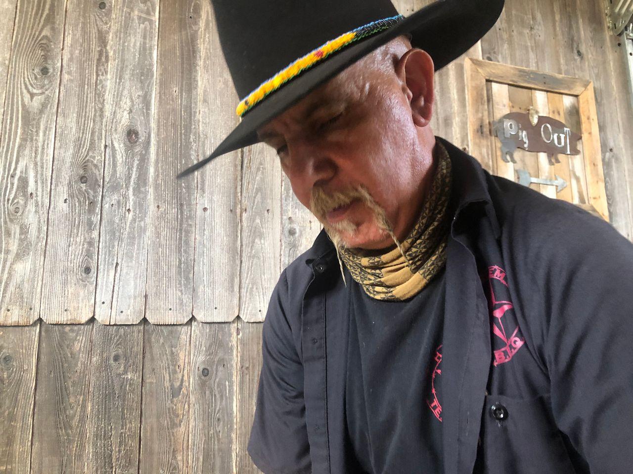 Ara Malekian seasons meat at Harlem Road Texas Barbecue. (Bryan Boes/Spectrum News)