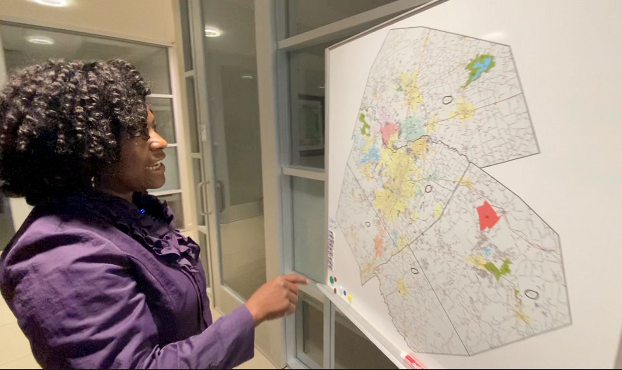 Abena Asante, senior program officer with the St. David's Foundation, studies a broadband access map in this image from June 2021. (Spectrum News 1/Matthew Mershon)