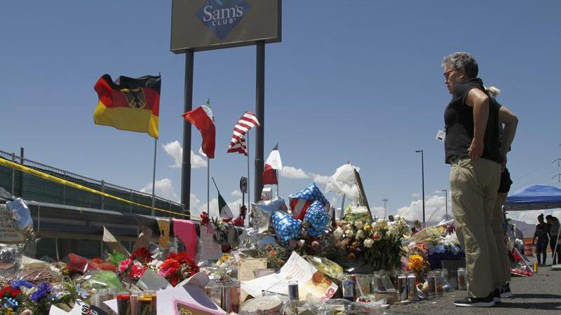 FILE - In this Aug. 12, 2019 photo, mourners visit the makeshift memorial near the Walmart in El Paso, Texas, where 22 people were killed in a mass shooting. (AP Photo/Cedar Attanasio, File)
