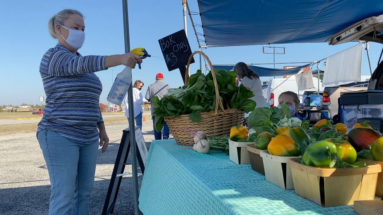 Laura Blaylock spraying veggies (Lupe Zapata/Spectrum News)
