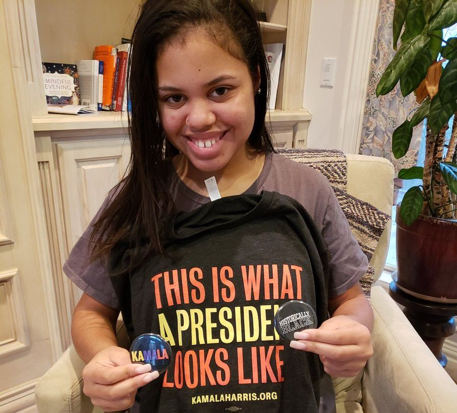 Haley poses wearing a Kamala Harris T-shirt and holding Harris buttons. (Lupe Zapata/Spectrum News 1)