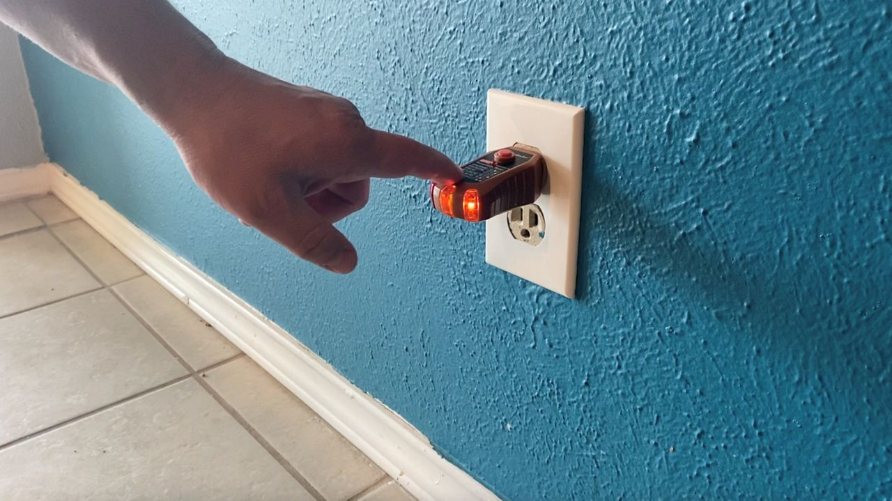 An electrical outlet is tested in this image from May 2021. (Spectrum News 1/Magaly Ayala)