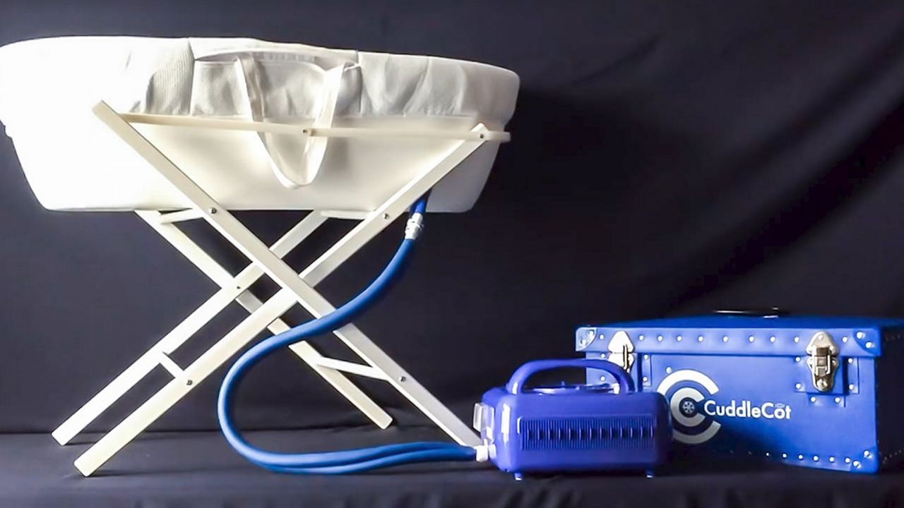 A Cuddle Cot device, which is a white bassinet, with a blue box with hoses