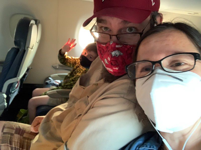 The Blaine sitting in an airplane with masks on.