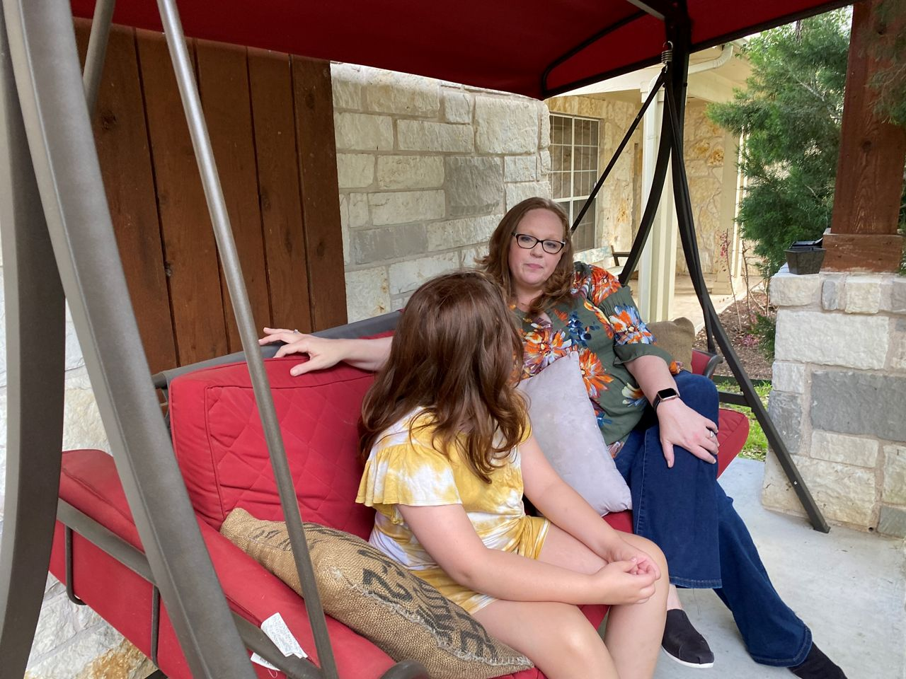 Tammy Heinz swinging on bench with daughter outside their Austin home. (Spectrum News 1/Monica Ortiz)