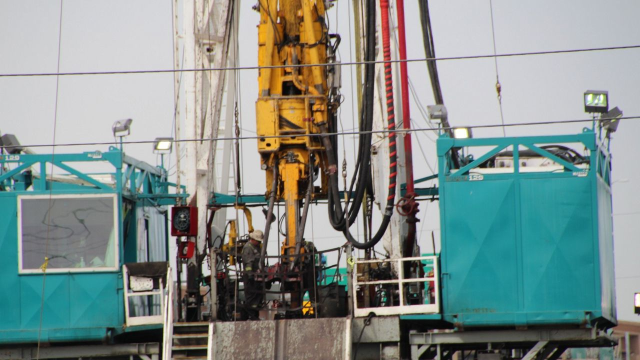 A worker stands on gas drilling site.