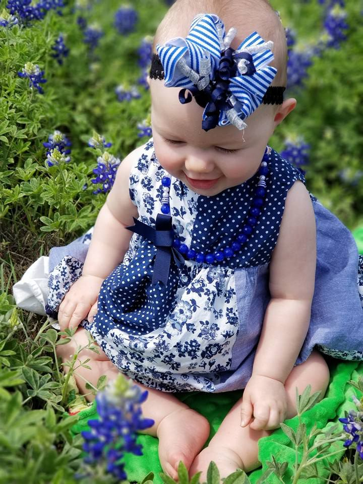 Baby girl sits in bluebonnet flower path.
