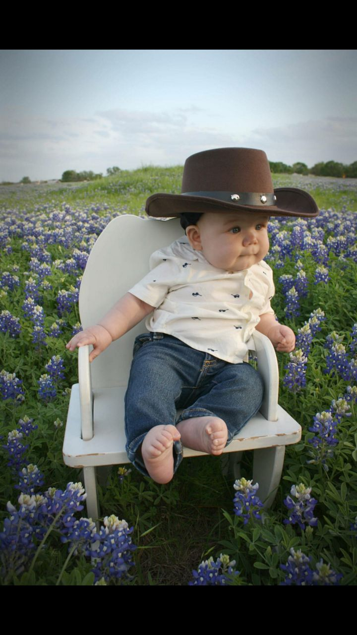 Baby with cowboy hat sits in wildflowers.