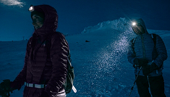 Man and woman walking through the snow in the dark wearing Columbia jackets