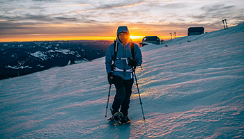 Man skiing at sunset in a Columbia jacket and pants