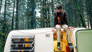 Man sitting on top of a vintage van wearing Columbia clothing in a forest