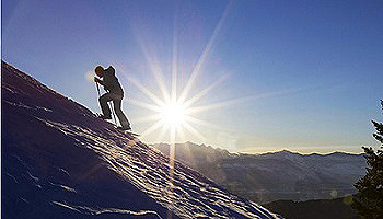 A man climbing up a mountain in the snow