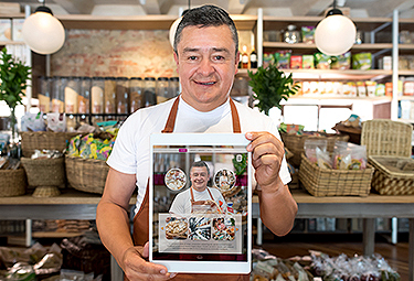 Man wearing apron reading Visa's digital transformation guide on a tablet device